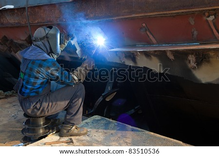 Welder in a protective mask when working.
