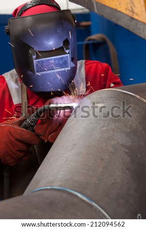 welder in factory with protective equipment welding pipe #212094562
