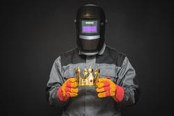 Welder in welding helmet with a golden crown award trophy in the hands. Best welder concept. Royal welding service.