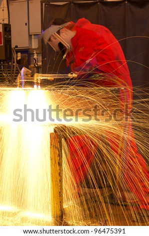 Welder in workshop manufacturing metal construction with multi-exposure blur on man