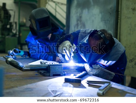 Welder master with trainee at work