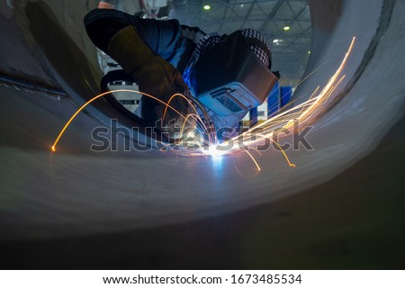 Welder performs welding work semi-automatic electric arc welding. Stainless steel pipe welding. Pipe production. MIG welding. Photo stock ©