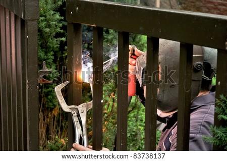 Welder repairing residential gate - stock photo