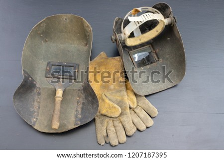 Welder's mask and gloves on a black workshop table. Protective clothing for workers in metalware. Dark background. #1207187395