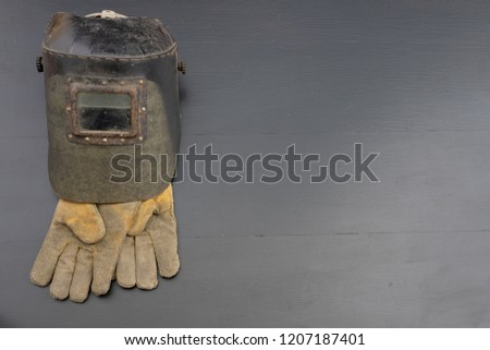 Welder's mask and gloves on a black workshop table. Protective clothing for workers in metalware. Dark background. #1207187401