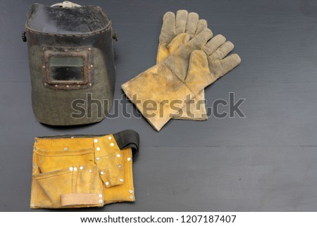 Welder's mask and gloves on a black workshop table. Protective clothing for workers in metalware. Dark background. #1207187407