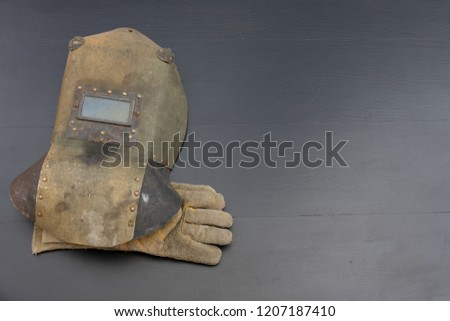 Welder's mask and gloves on a black workshop table. Protective clothing for workers in metalware. Dark background. #1207187410