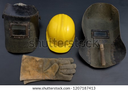 Welder's mask and gloves on a black workshop table. Protective clothing for workers in metalware. Dark background. #1207187413