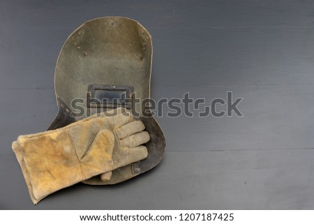 Welder's mask and gloves on a black workshop table. Protective clothing for workers in metalware. Dark background. #1207187425