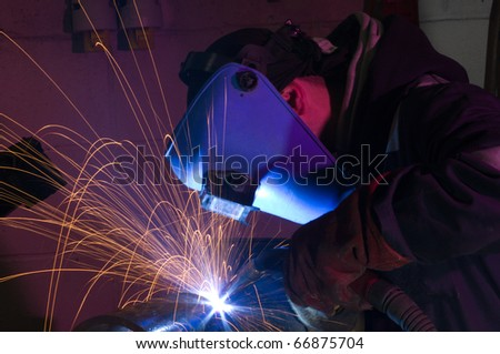 Welder uses MIG torch to make sparks during manufacture of metal equipment. - stock photo