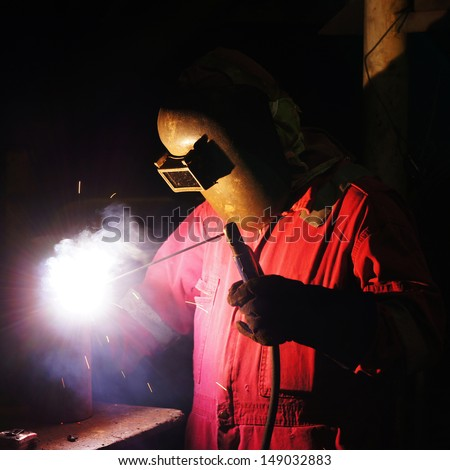 Welder uses torch to make sparks to weld metal equipment - Square Format