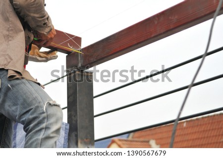 Welder using measuring tape to measure iron while building steel roof in house renovation job. Worker in construction industry. #1390567679