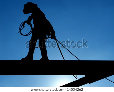 Welder walks the high steel at a construction site - stock photo