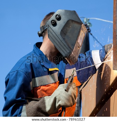 Welder wearing a mask while working outdoors