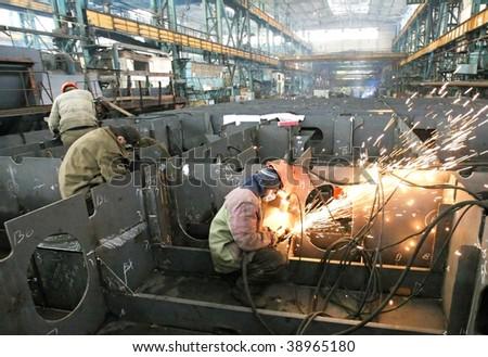 Welder welding a metal part in a dark industrial environment.