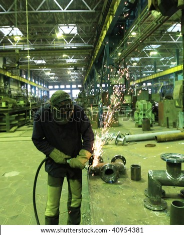 Welder welding a metal part in a dark industrial environment. - stock photo