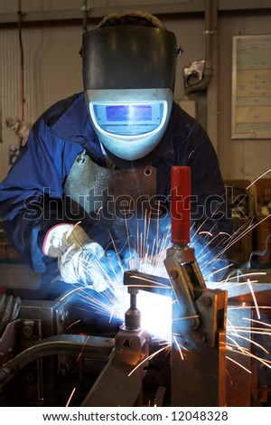 Welder welding a metal part in an industrial environment, wearing standard protection equipment. Sparks flying, fumes, industrial background