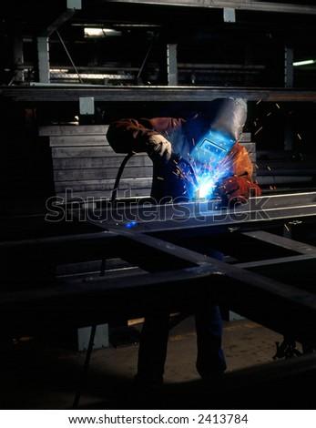 Welder welding metal in shop