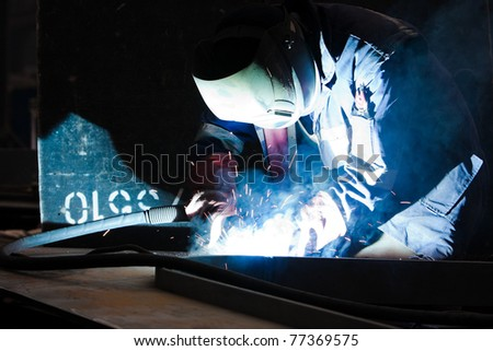 welder with protective equipment in factory