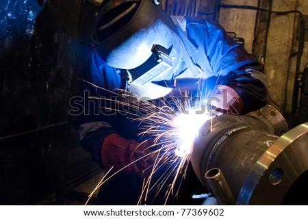 welder with protective equipment in factory