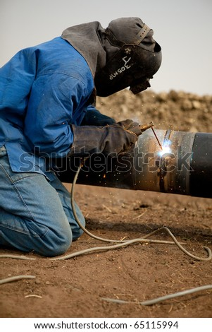 Welder worker fixing industrial construction oil and gas plumbing pipeline