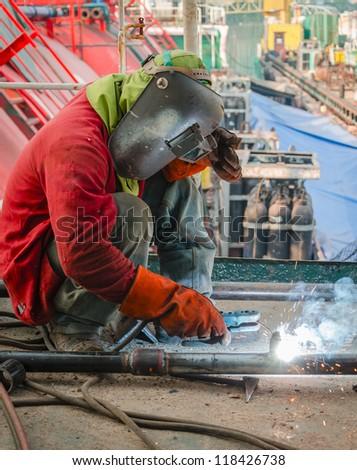 welder worker welding metal at construction site
