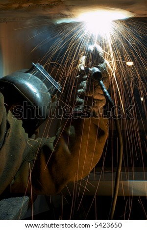 welder working at night has sparks fly #5423650