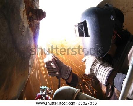 Welder working on home water tank