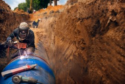Welder working welding pipeline underground installation in construction site wearing safety mask equipment for protective accident from work.