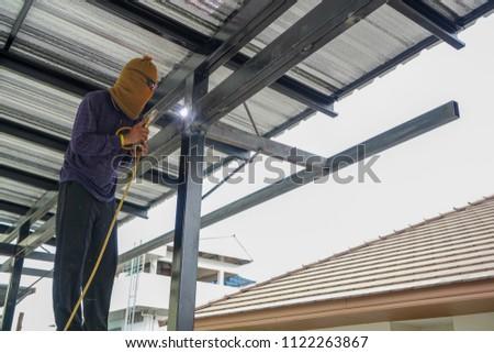 Welders are welding steel roof frame of home #1122263867