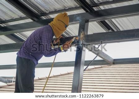 Welders are welding steel roof frame of home #1122263879
