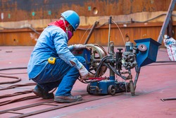 Welding male worker control surfacing of tank bottom plate steel roll by slag submerged arc welding process.