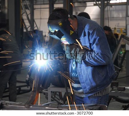 welding operator holding his mask