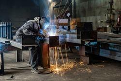 Welding with sparks by Process fluxed cored arc welding ,Industrial steel welder part in factory welder Industrial automotive part in factory.