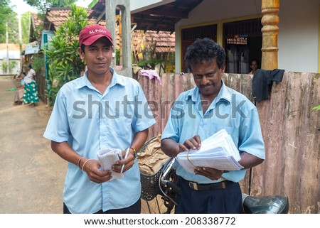 WELIGAMA, SRI LANKA - MARCH 8, 2014: Two postmen delivering post to local people. Sri Lanka Posts has been in existence for more than 209 years and employs more than 17,000 employees.