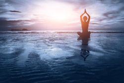well being concept, beautiful sunset on the beach, woman practicing yoga