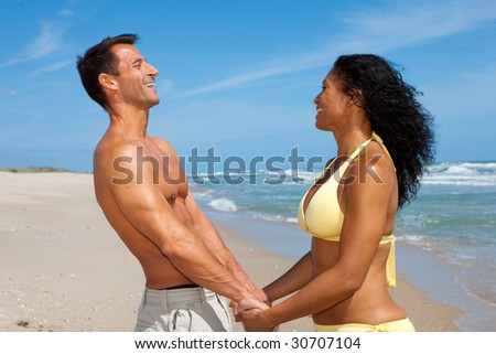 Well build couple standing at the beach, having fun