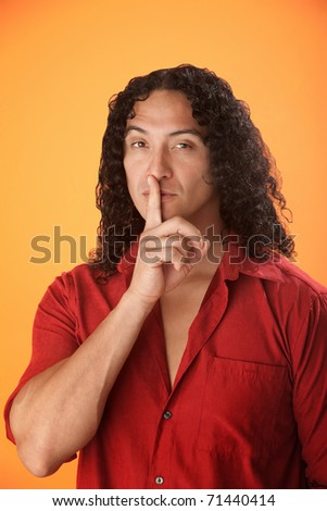 Well built Hispanic man with finger to his lips