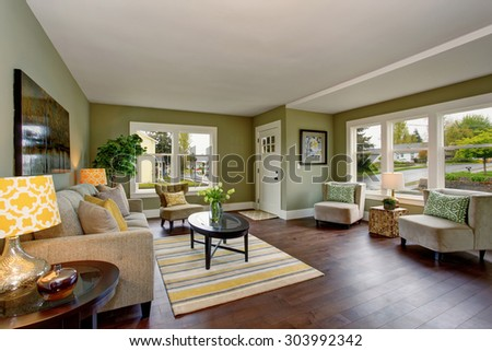 Well decorated living room with hardwood floor, and green yellow theme.