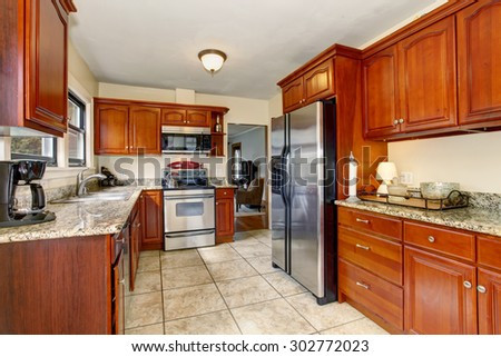 Well defined kitchen with large tile floor, and stained cabinets.