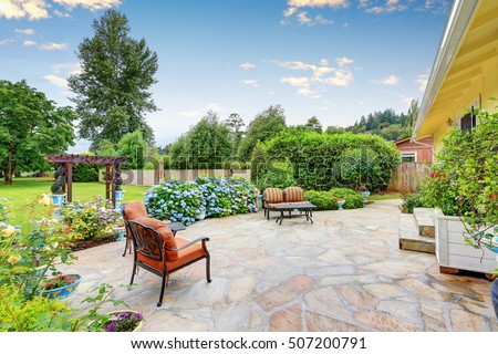 Well designed patio area with stone floor in the backyard of a yellow house. Relaxing area with comfortable outdoor furniture and blooming hydrangea flowers. Northwest, USA