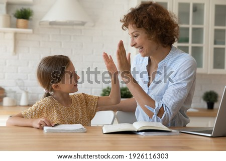 Well done dear. Excited mother give high five to small daughter praise child for reaching success in homework. Joyful female tutor greet schoolgirl for giving correct answer solving hard math problem