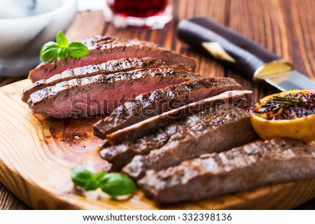 Well-done grilled marinated beef flank steak on wooden board