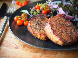 Well done grilled pork chop steak in black plate and vegetable salad on side