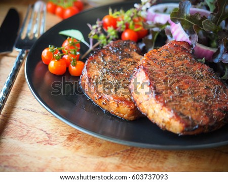 Well done grilled pork chop steak in black plate and vegetable salad on side
