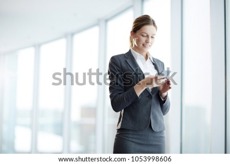 Well-dressed agent with smartphone reading message and texting inside modern business center #1053998606
