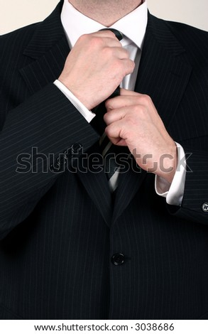 Well dressed business man adjusting his tie for a meeting