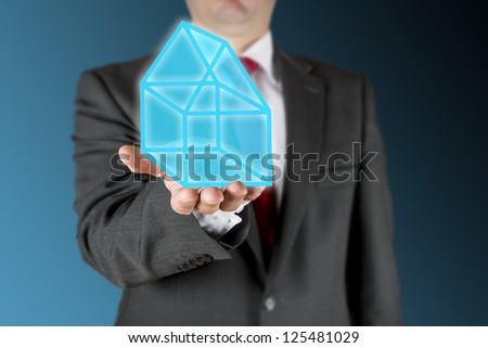 Well dressed business man is showing a illustrated blue house on his outstretched arm. Background is blue/black.