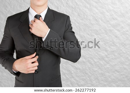 Well dressed businessman looklike smart adjusting  his neck tie on color background : fill text #262277192