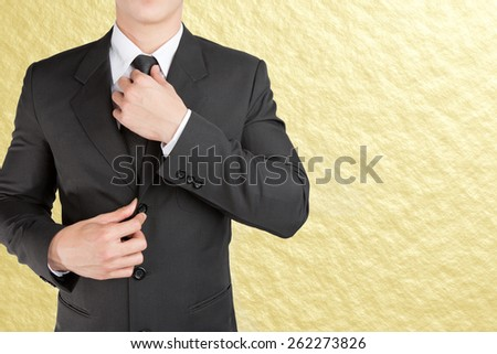 Well dressed businessman looklike smart adjusting  his neck tie on gold background : fill text